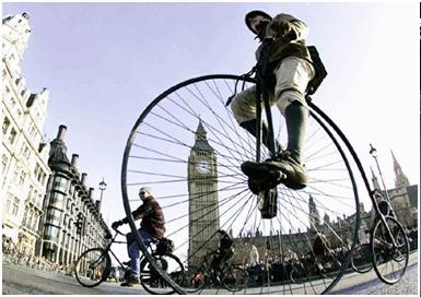 عبور يك دوچرخه سوار با دوچرخه بزرگ از مقابل پارلمان بريتانيا – لندن